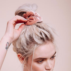 La Vie En Rose Scrunchie styled in a loose bun on a model with her hand touching it