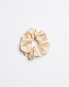 a Cowgilr in the Sand silk Scrunchie in a cream color from I'm With the Band laying flat