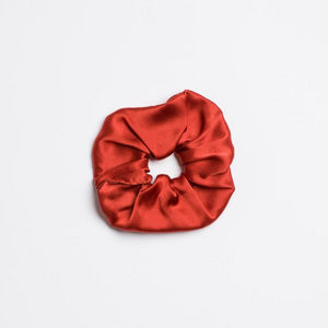 Rusty orange red colored Mojave Scrunchie from I'm With the Band laying flat