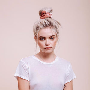 La Vie En Rose Scrunchie styled on a model wearing a large loose bun on the top of her head