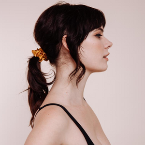 Side view of model wearing a Marigold Mini Scrunchie in a low ponytail