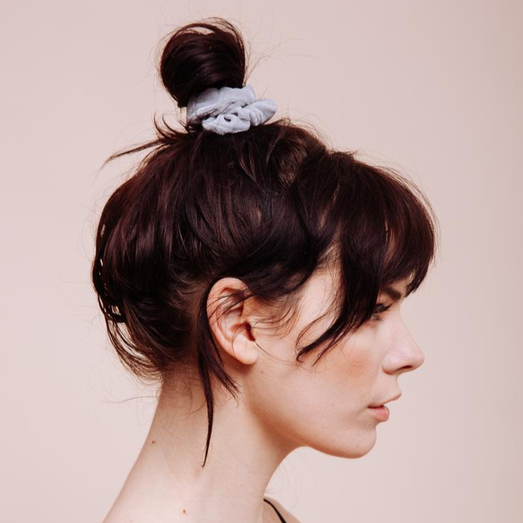 Light grey velvet Silverado Mini Scrunchie styled in a messy top bun side view close up