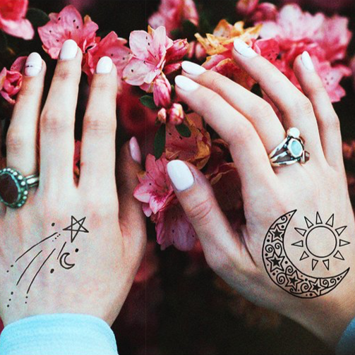 The Cosmic Pack Temporary Tattoos from Inked by Dani styled on a model's hands