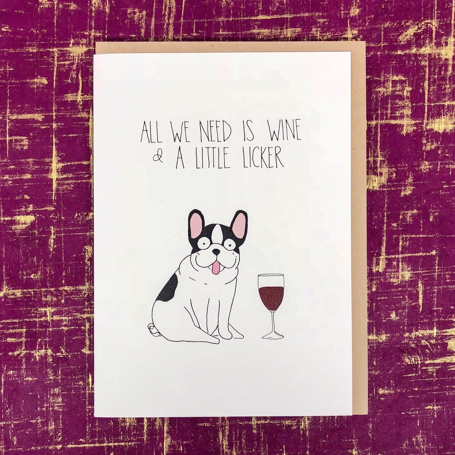 "White background with a little black and white dog with a glass of wine that says ""All we need is wine and a little licker""."
