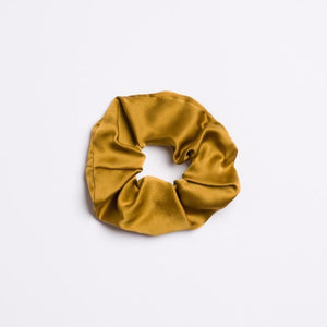 Golden Canyon Scrunchie which is silk and a brownish yellow color from I'm With the Band laying flat