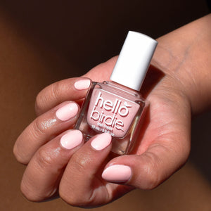 A close up of a mid toned hand comes in from the upper right corner holding a bottle of Nest Friends Forever nail polish from Hello Birdie. The polish is worn on the nails and is a light peach hue. The bottle is a cube shape and has a white cap and white text and logo. The background is brown and the light falls off towards the upper right corner.