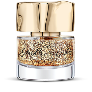Large and small gold glitter particles suspended in clear base Smith & Cult nail polish bottle with dented gold cap
