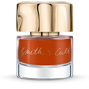 Opaque Burnt Orange Smith & Cult nail polish bottle with gold dented cap