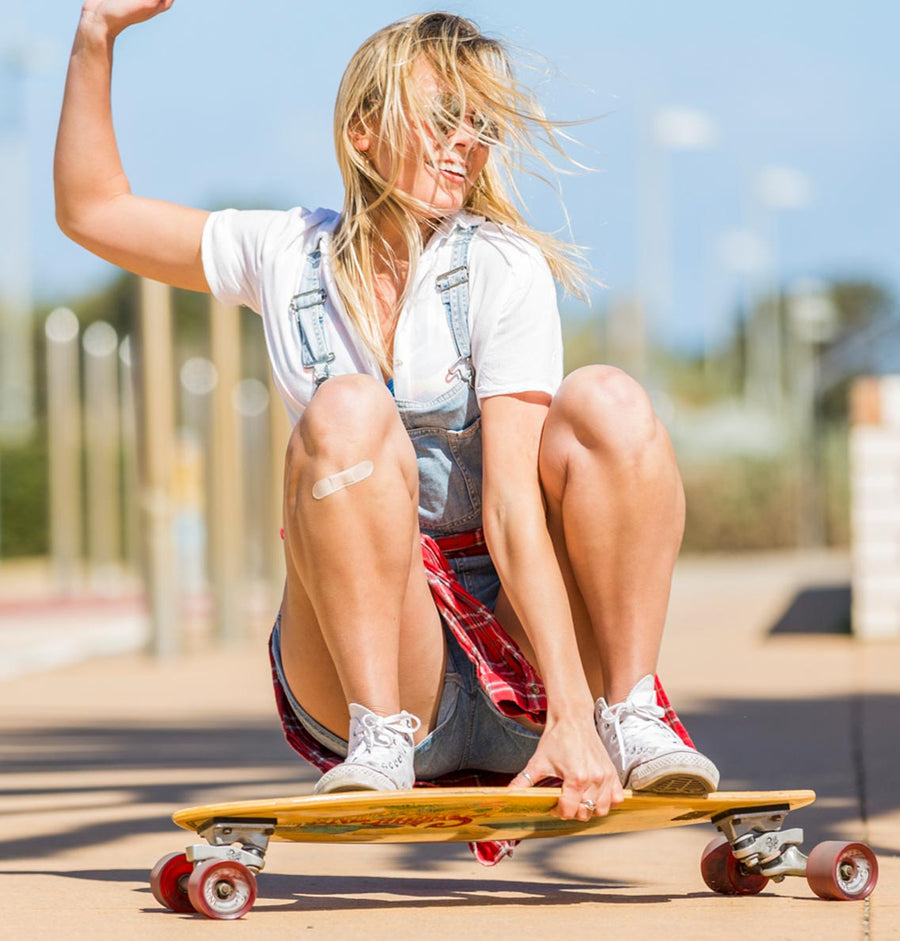 Young female skateboarder laughing and wearing light bamboo Patch strip on knee