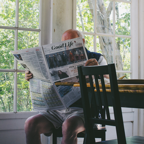 Man reading the newspaper, ongoing research for CBD as a treatment and relief for cancer symptoms