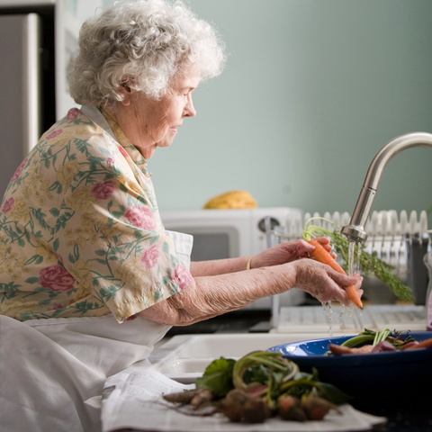 Health concerns for the elderly, beautiful elderly woman washing vegetables in kitchen