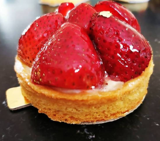 Fresh strawberry tart decorated with gold leaf