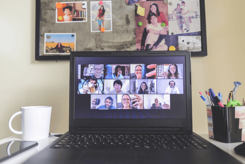 a group of friends offering a 'cheers' over video chat on a laptop