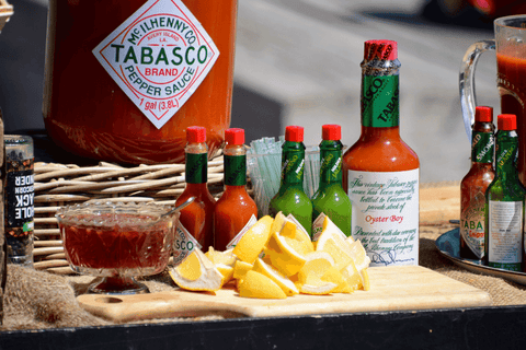 assorted hot sauces sitting on table with lemon and dishes