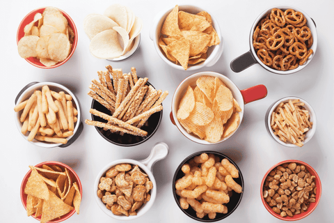 assorted snacks in bowls in table salty pretzels chips