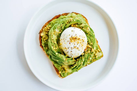 avocado toast with poached egg food art green white plate seasoning