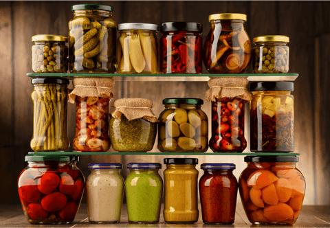 differently colored jars of pickles and vegetables