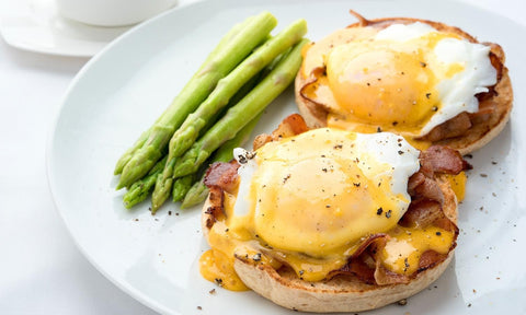 eggs Benedict with asparagus pepper bacon english muffin brunch white plate