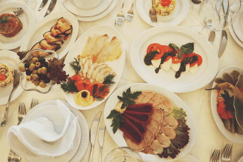 many serving dishes on the table with tomatoes olives and other foods