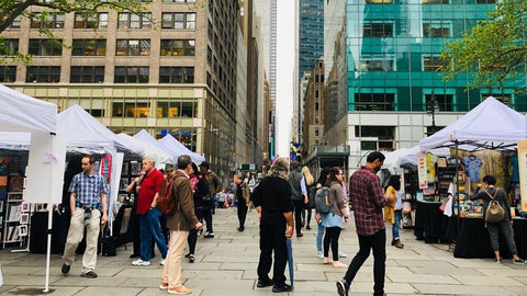 people congregating in new york city vendors market pop up skyscrapers clouds
