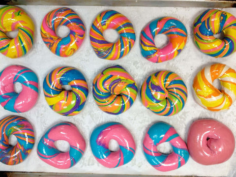 rainbow bagel shiny pink and blue swirl several many on a baking sheet