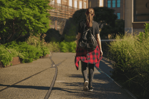 young girl backpack train tracks plants city scape flannel shirt jeans brown hair windows sunset