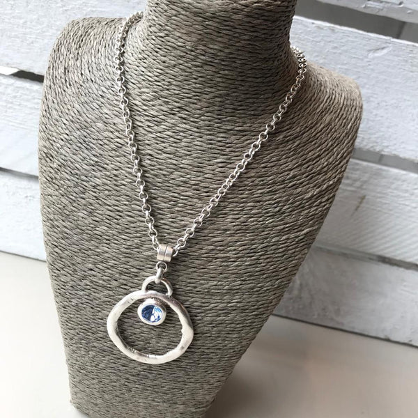 Silver necklace with circular pendent and blue crystal