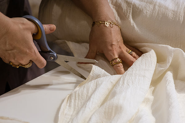 hands of a person cutting white fabric with scissors