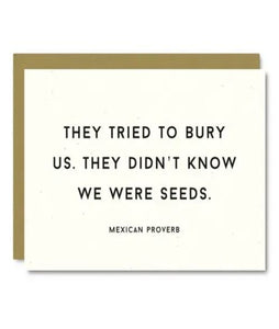"Pictured against a white background is a white card that says, ""They tried to bury us. They didn't know we were seeds."" with the text ""Mexican proverb"" underneath. There is a brown enveloped placed behind the white card."