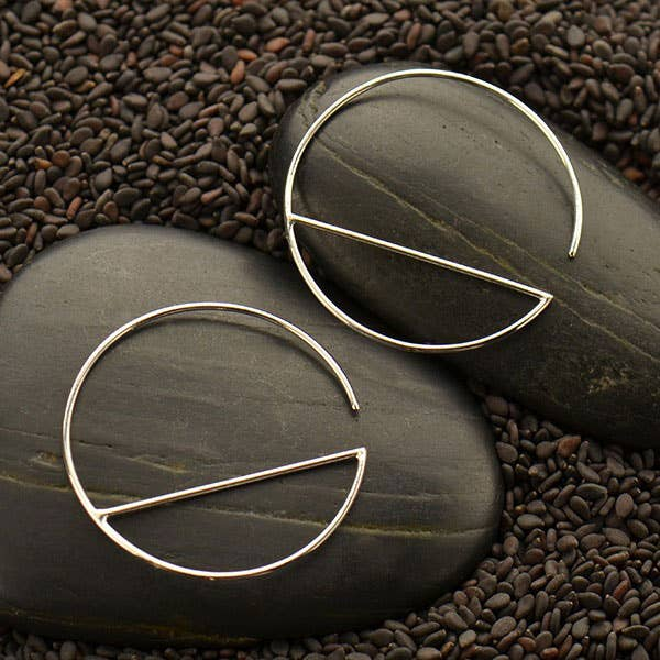 Close up of hoop hook earrings with a vertical line running through the circle shape. Against two black stones and tiny black pebbles.