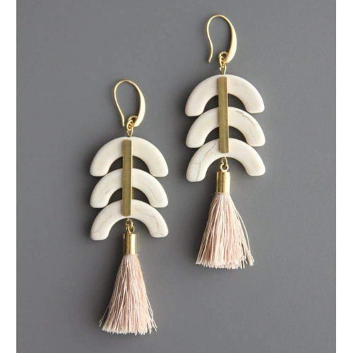 drop earrings with brass elements, 3 half moon magnesite pieces, and a light pink silk tassel. 18k gold plated brass hooks. Against a grey background