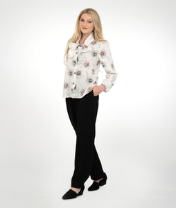 model in black slim pants and a white blouse with a black and red rose print. Blouse has ties at the neckline that can be worn loose or tied