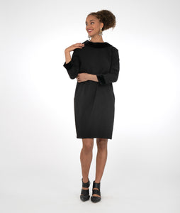 model in a black knee length dress with a velvet collar and sleeve cuffs. Collar is round in the front and comes to a split in the back on a v-neckline.