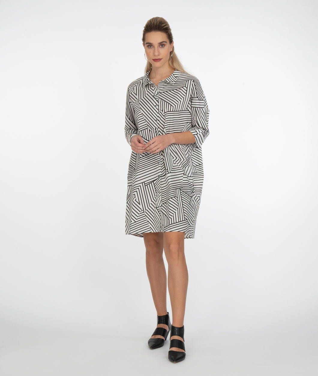 model in a black and white striped button up dress in front of a white background