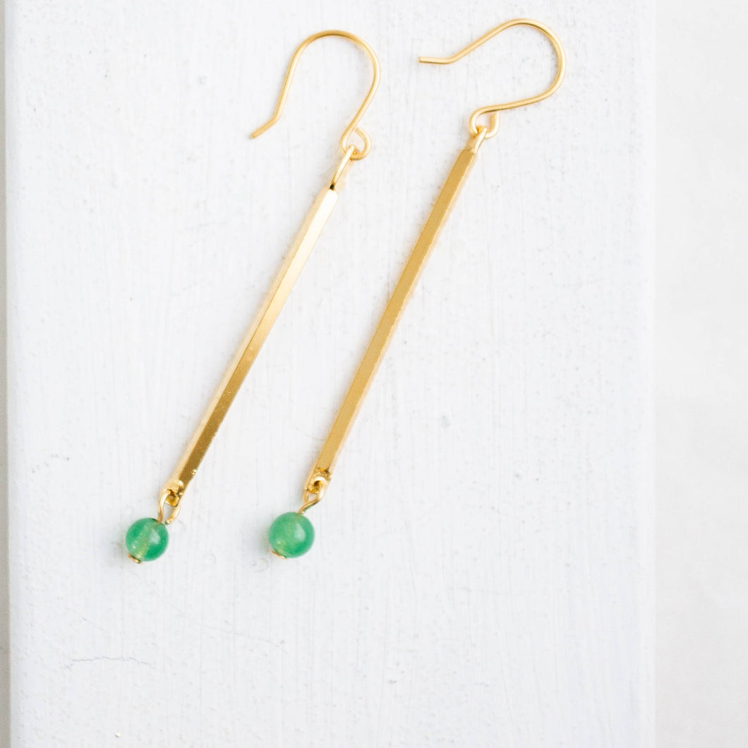Brass skinny hanging earrings with a small green bead at the base.
