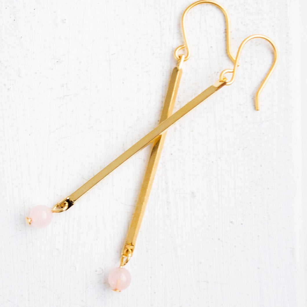 A pair of brass stick earrings with a small pink bead at the base.