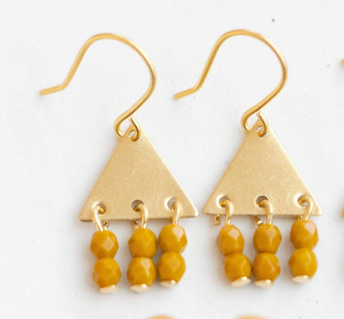 close up of tiny brass triangle earrings with 3 sets of 2 faceted beads dangliong below. One a gold tone ear hook, against a white background.