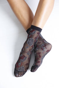 model in a black sheer sock with a red and silver metallic pattern