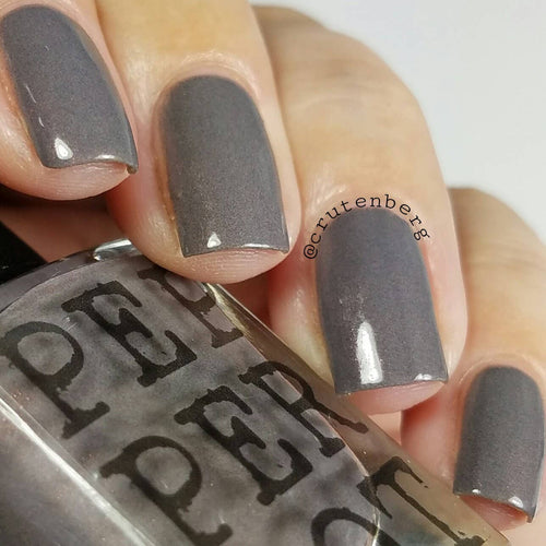 grey polished nails holding a bottle of nail polish