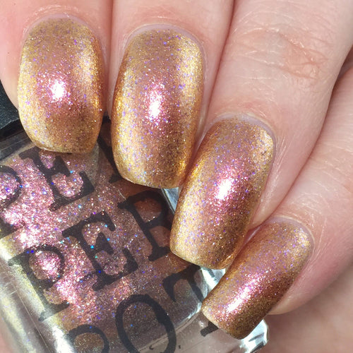 glittery gold polished nails holding a bottle of nail polish