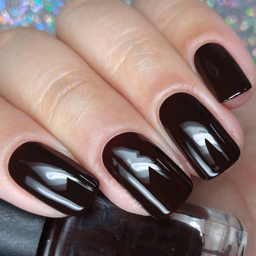 dark polished nails holding a bottle of nail polish