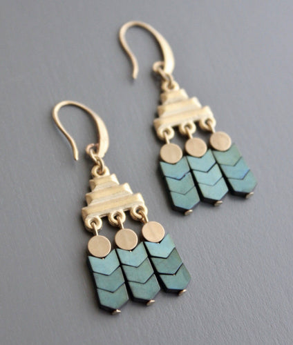 This elegant, lightweight drop earring is made with an 18k gold plated brass hook, plated hematite and brass. Brass pyramid element with 3 drops of 3 verdigris chevron beads and brass disc. Against a grey background