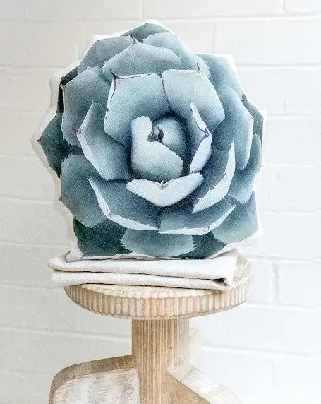Succulent shaped pillow made out of linen canvas material sitting atop a wooden stool against a white brick background