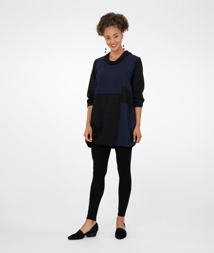 model in black leggings and a black and navy color block tunic with a cowl neck