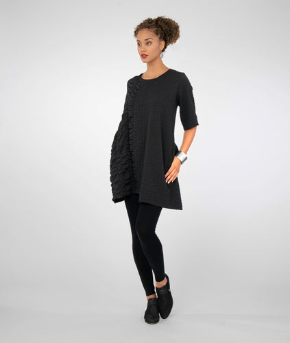 model in black leggings with a black textured tunic with an uneven hemline
