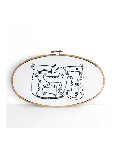 oval embroidery hoop with black thread with a stylized group of cat illustrations against a white background