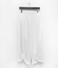 Load image into Gallery viewer, a pair of white pants hanging from a black hanger. The pants have a full elastic waistband and a wide cuff at the pant hem with a tulip shaped overlay in the front center of each leg