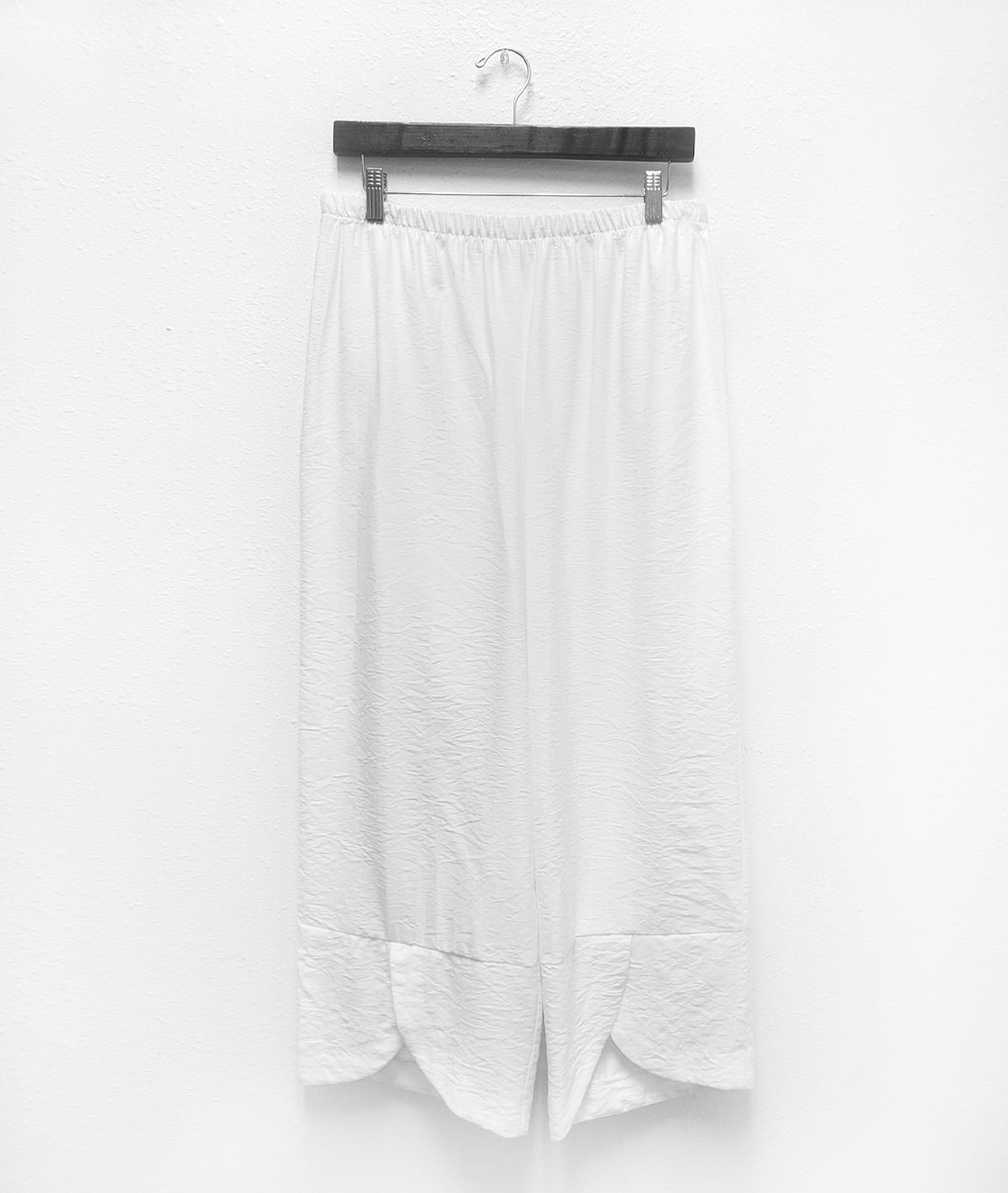 a pair of white pants hanging from a black hanger. The pants have a full elastic waistband and a wide cuff at the pant hem with a tulip shaped overlay in the front center of each leg