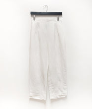Load image into Gallery viewer, a slim white pant with an uneven hem on a black hanger