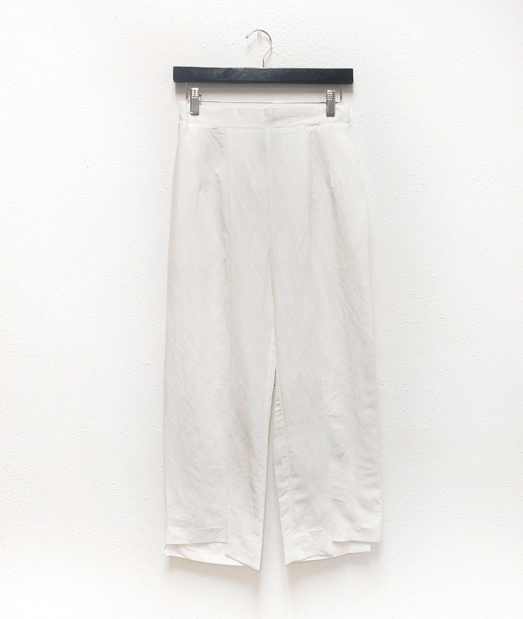a slim white pant with an uneven hem on a black hanger